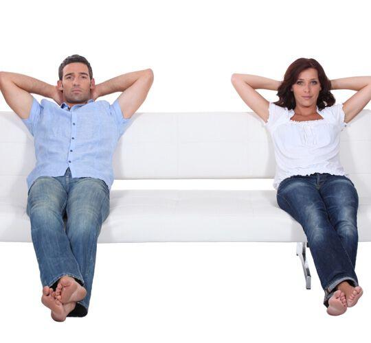 Couple sitting apart on white sofa