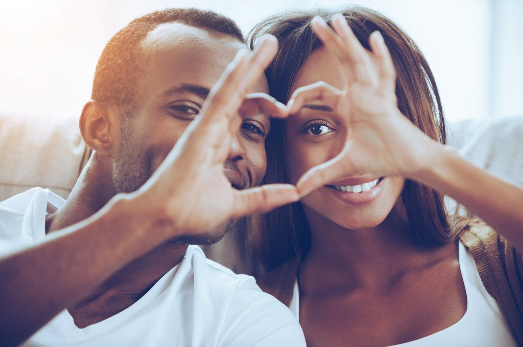 African American couple making a heart sign with their fingers